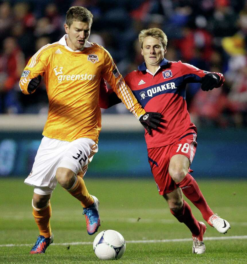 Houston Dynamo defender Bobby Boswell (32) and Chicago Fire forward Chris Rolfe (18) battle for the ball during the first half of their playoff MLS soccer match, Wednesday, Oct. 31, 2012, in Bridgeview, Ill. (AP Photo/Nam Y. Huh) Photo: Nam Y. Huh, Associated Press / AP
