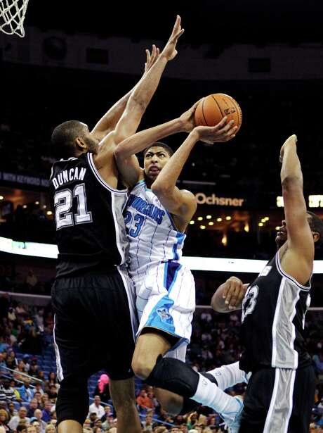 Differing NBA generations collide as Hornets rookie Anthony Davis (23) runs into Tim Duncan. Photo: Gerald Herbert, STF / AP