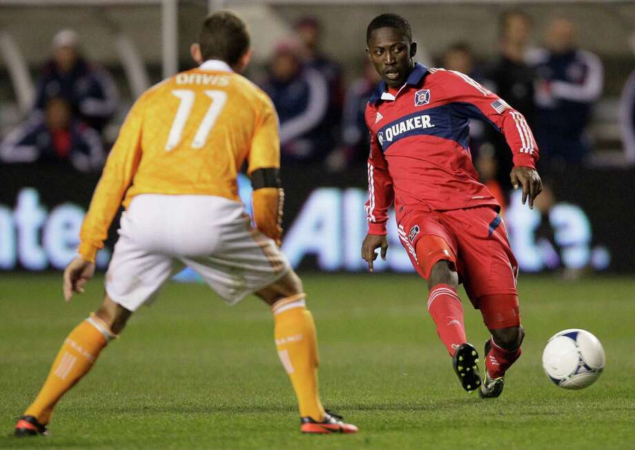 Chicago Fire midfielder Patrick Nyarko (14) passes the ball against Houston Dynamo midfielder Brad Davis (11) during the second half of an MLS soccer playoffs on Wednesday, Oct. 31, in Bridgeview, Ill. The Dynamo won 2-1. (AP Photo/Nam Y. Huh) Photo: Nam Y. Huh, Associated Press / AP