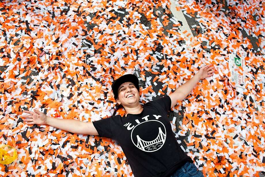 Katy Juranty makes a confetti angel on Market Street after the Giants World Series Championship parade in San Francisco, Calif., Wednesday, October 31, 2012. Photo: Jason Henry, Special To The Chronicle