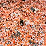 An empty liquor bottle sits on Market Street amid a sea of confetti after the Giants World Series Championship parade in San Francisco, Calif., Wednesday, October 31, 2012.