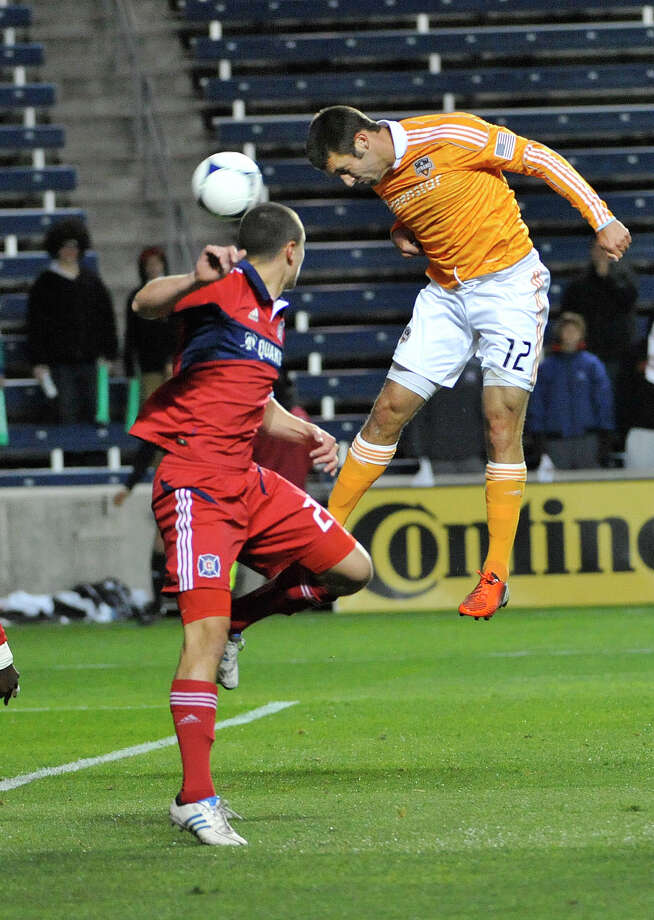 The Fire's Austin Berry, left, is helpless to stop Dynamo forward Will Bruin from scoring his first goal in the 12th minute. Brad Davis picked up the assist. Photo: David Banks, Stringer / Getty Images North America