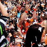 Parade goers play in confetti after the Giants World Series Championship parade in San Francisco, Calif., Wednesday, October 31, 2012.
