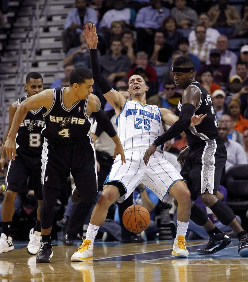 San Antonio Spurs shooting guard Danny Green (4) and small forward Stephen Jackson (3) strip the ball from New Orleans Hornets shooting guard Austin Rivers (25) in the second half of an NBA basketball game in New Orleans, Wednesday, Oct. 31, 2012. The Spurs won 95-99. (AP Photo/Gerald Herbert) (Associated Press)