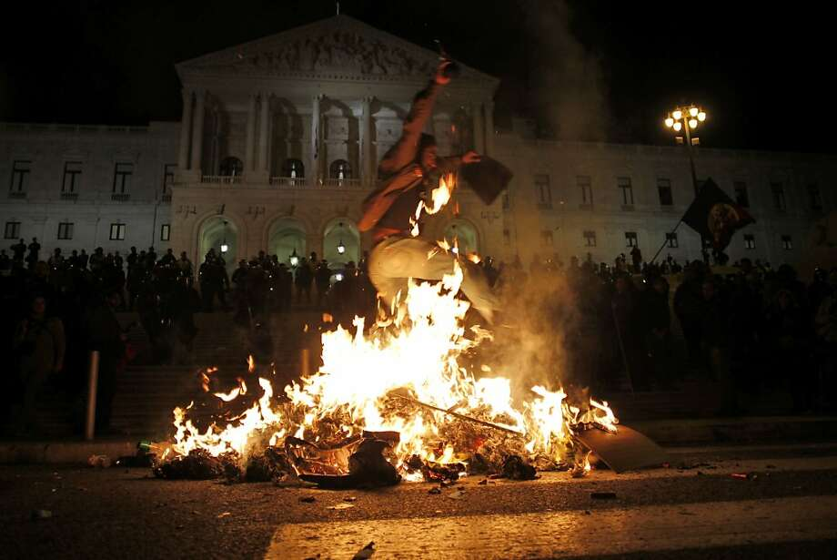 A man jumps over a fire, set by demonstrators during a protest outside the Portuguese parliament in Lisbon, Wednesday, Oct. 31 2012, against the government's proposed 2013 state budget.  The spending plan will include an increase in taxes as well as further cuts in public services and civil service layoffs. (AP Photo/Francisco Seco) Photo: Francisco Seco, Associated Press
