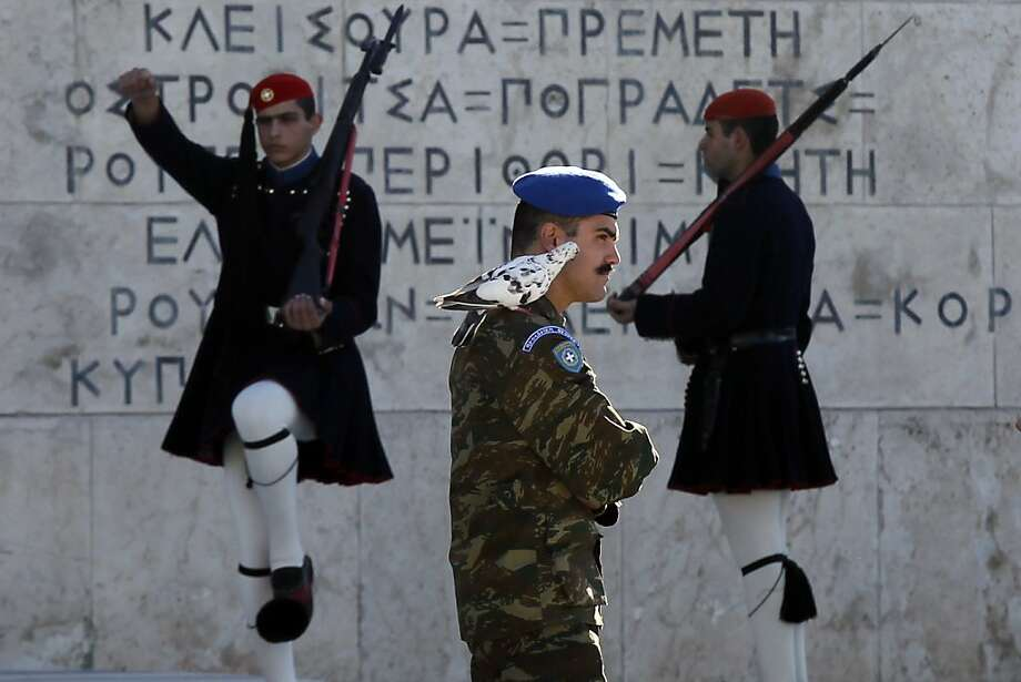 A pigeon sits on the shoulder of a Greek Presidential Guard as his colleagues in traditional Evzones' costumes perform ceremonial duties at the tomb of the unknown soldier in Athens, Wednesday, Oct. 31 2012. Greece's two main labor unions covering civil servants and the private sector have called a 48-hour strike to protest austerity measures due to be voted on next week. The strike call came as the finance minister submitted an amended 2013 budget that raised the country's debt and deficit forecasts for next year. (AP Photo/Kostas Tsironis) Photo: Kostas Tsironis, Associated Press