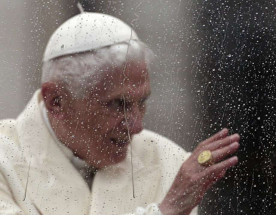 Pope Benedict XVI is seen behind a window covered in raindrops as he delivers his blessing from his pope-mobile in St. Peter's Square at the end of his general audience, at the Vatican, Wednesday, Oct. 31, 2012. (AP Photo/Gregorio Borgia) Photo: Gregorio Borgia, Associated Press