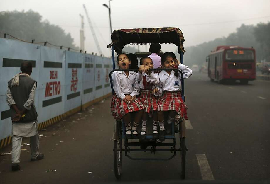 An Indian schoolgirl yawns as she rides with friends to school on a bicycle rickshaw in New Delhi, India, Wednesday, Oct. 31, 2012. (AP Photo/Kevin Frayer) Photo: Kevin Frayer, Associated Press