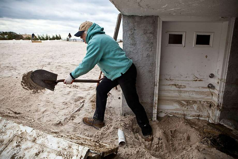 Barbara Young digs sand out from her front door, which was caused by Hurricane Sandy, on October 31, 2012 in Long Beach, New York.The storm has claimed many lives in the United States and has caused massive flooding across much of the Atlantic seaboard. U.S. President Barack Obama has declared the situation a 'major disaster' for large areas of the U.S. east coast, including New York City, with widespread power outages and significant flooding in parts of the city.  (Photo by Andrew Burton/Getty Images) Photo: Andrew Burton, Getty Images