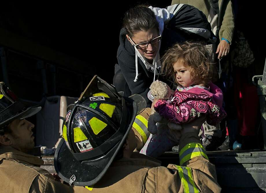 On a National Guard truck, Ali LaPointe, of Hoboken, N.J., hands her daughter Eliza Skye LaPointe, 18-months-old, to Hoboken firefighters, Wednesday, Oct. 31, 2012, in Hoboken, N.J., in the wake of superstorm Sandy. Some residents are being plucked from their homes by large trucks as parts of the city are still covered in standing water. (AP Photo/Craig Ruttle) Photo: Craig Ruttle, Associated Press