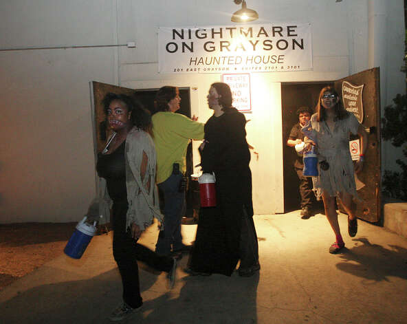 After the last of the crowds leaves Nightmare on Grayson, employees exit for a group photo, Wednesday, Oct. 31, 2012. The event is schedule to move out of the East Grayson Street location for the next run. Friday and Saturday night are the last shows on scheduled. Photo: Jerry Lara, San Antonio Express-News / San Antonio Express-News