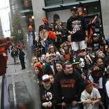 Maintenance and guest services employees reflected in a mirror wave throw candy and swing rally towels to fans gathered on Market Street as they watch the  the San Francisco Giants World Series victory parade on Wednesday, October 31, 2012 in San Francisco, Calif.