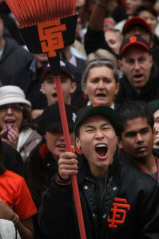 A Giants fan with a broom watches Wednesday's victory parade, honoring the World Series sweep of the Tigers. Photo: Lea Suzuki, The Chronicle