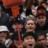 A San Francisco Giants fan holds a broom in the air as he watches the   San Francisco Giants World Series victory parade pass on Wednesday, October 31, 2012 in San Francisco, Calif.
