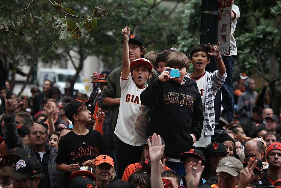 San Francisco Giants fans wave and cheer as they watch the San Francisco Giants World Series victory parade pass on Market Street on Wednesday, October 31, 2012 in San Francisco, Calif. Photo: Lea Suzuki, The Chronicle