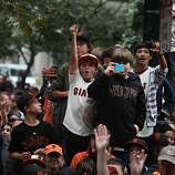 San Francisco Giants fans wave and cheer as they watch the San Francisco Giants World Series victory parade pass on Market Street on Wednesday, October 31, 2012 in San Francisco, Calif.