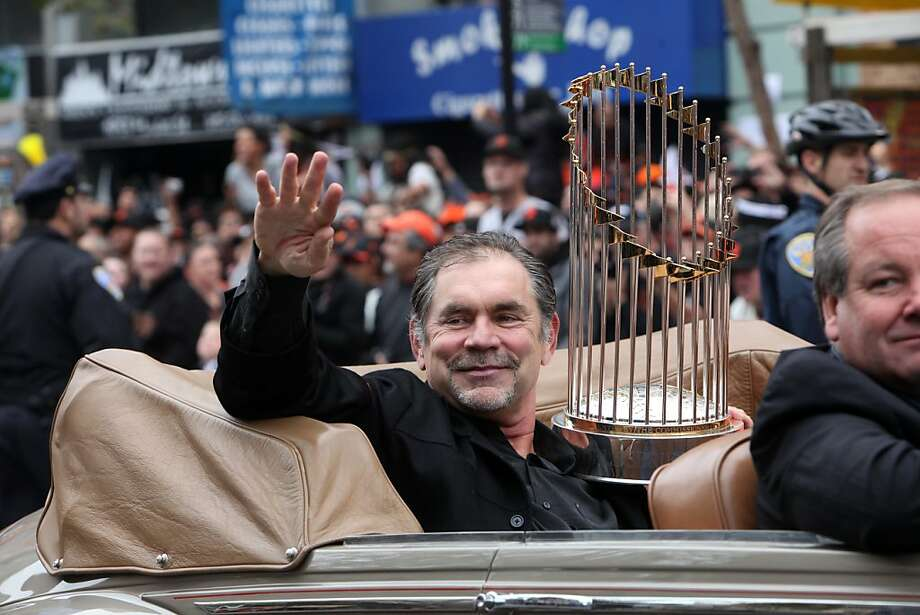 Giants manager Bruce Bochy carries the World Series trophy as he waves to fans along the parade route during the San Francisco Giants World Series victory parade on Wednesday, October 31, 2012 in San Francisco, Calif. Photo: Lea Suzuki, The Chronicle