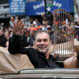 Giants manager Bruce Bochy carries the World Series trophy as he waves to fans along the parade route during the San Francisco Giants World Series victory parade on Wednesday, October 31, 2012 in San Francisco, Calif.