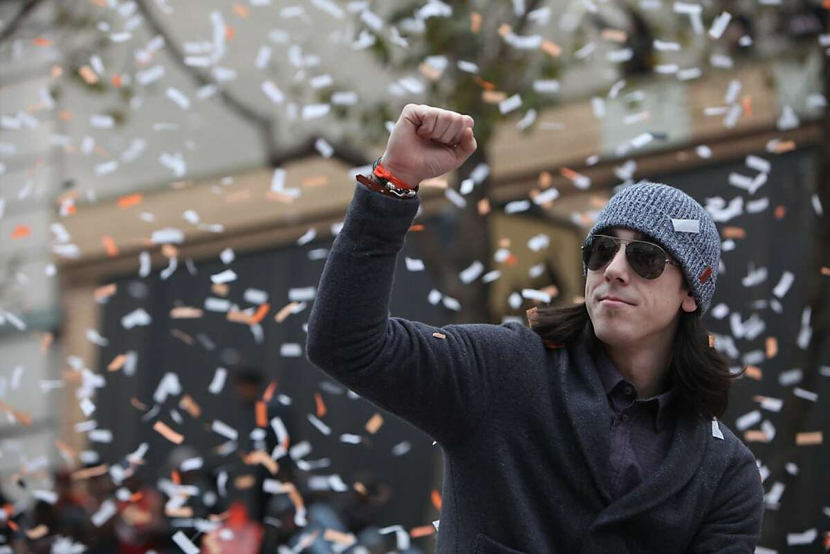 Giants pitcher Tim Lincecum pumps his fist as he rides through confetti along the parade route during the San Francisco Giants World Series victory parade on Wednesday, October 31, 2012 in San Francisco, Calif.