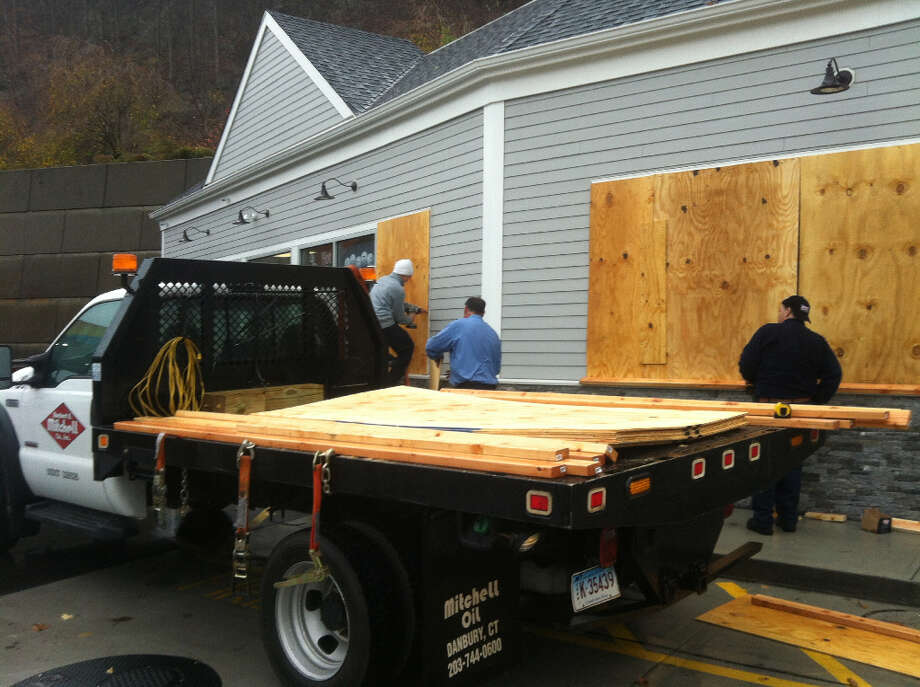 The owner of a Sunoco on Federal Road that was renovated just about four months ago decided not to take any chances and began installing plywood sheets on the windows around 2 p.m. Monday as winds began to pick up in the Danbury area. (Dirk Perrefort)