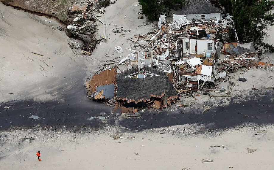 MANTOLOKING, NJ - OCTOBER 31:  A woman walks on the beach past homes destroyed by Hurricane Sandy on October 31, 2012 in Mantoloking, New Jersey.  At least 50 people were reportedly killed in the U.S. by Sandy with New Jersey suffering massive damage and power outages. Photo: Mario Tama, Getty Images / 2012 Getty Images