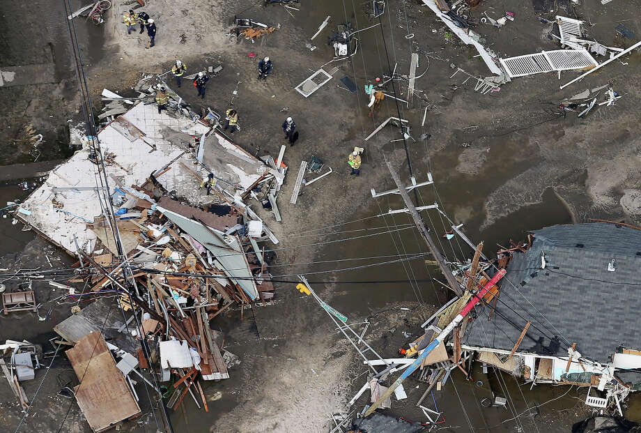 SEASIDE HEIGHTS, NJ - OCTOBER 31: Rescue workers stand around a home wrecked by Superstorm Sandy on October 31, 2012 in Seaside Heights, New Jersey. At least 50 people were reportedly killed in the U.S. by Sandy with New Jersey suffering massive damage and power outages. Photo: Mario Tama, Getty Images / 2012 Getty Images