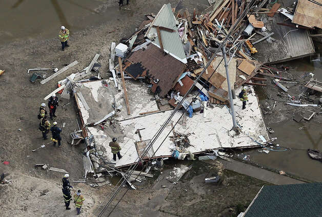 SEASIDE HEIGHTS, NJ - OCTOBER 31: Rescue workers gather around a house wrecked by Superstorm Sandy on October 31, 2012 in Seaside Heights, New Jersey. At least 50 people were reportedly killed in the U.S. by Sandy with New Jersey suffering massive damage and power outages. Photo: Mario Tama, Getty Images / 2012 Getty Images