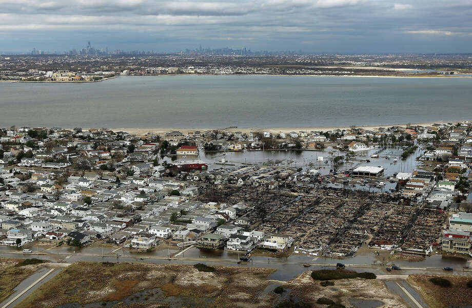 NEW YORK, NY - OCTOBER 31: The remains of burned homes (Bottom R) are surrounded by water with the Manhattan skyline in the distance after Superstorm Sandy on October 31, 2012 in the Breezy Point neighborhood of the Queens borough of New York City. Over 50 homes were reportedly destroyed in a fire during the storm. At least 50 people were reportedly killed in the U.S. by Sandy. New York City was hit especially hard with widespread power outages and significant flooding in parts of the city. Photo: Mario Tama, Getty Images / 2012 Getty Images
