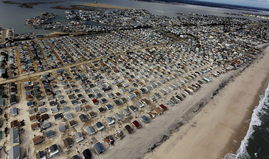 SEASIDE HEIGHTS, NJ - OCTOBER 31: Homes are surrounded by sand washed in by Superstorm Sandy on October 31, 2012 in Seaside Heights, New Jersey. At least 50 people were reportedly killed in the U.S. by Sandy with New Jersey suffering massive damage and power outages. Photo: Mario Tama, Getty Images / 2012 Getty Images