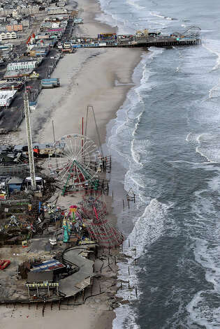 SEASIDE HEIGHTS, NJ - OCTOBER 31:  Waves break in front of two destroyed amusement parks wrecked by Superstorm Sandy on October 31, 2012 in Seaside Heights, New Jersey. At least 50 people were reportedly killed in the U.S. by Sandy with New Jersey suffering massive damage and power outages. Photo: Mario Tama, Getty Images / 2012 Getty Images