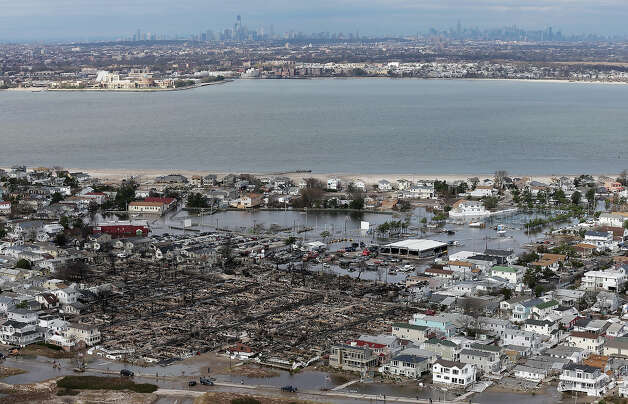 NEW YORK, NY - OCTOBER 31: The remains of burned homes (Bottom L) are surrounded by water with the Manhattan skyline in the distance after Superstorm Sandy on October 31, 2012 in the Breezy Point neighborhood of the Queens borough of New York City. Over 50 homes were reportedly destroyed in a fire during the storm. At least 50 people were reportedly killed in the U.S. by Sandy. New York City was hit especially hard with widespread power outages and significant flooding in parts of the city. Photo: Mario Tama, Getty Images / 2012 Getty Images
