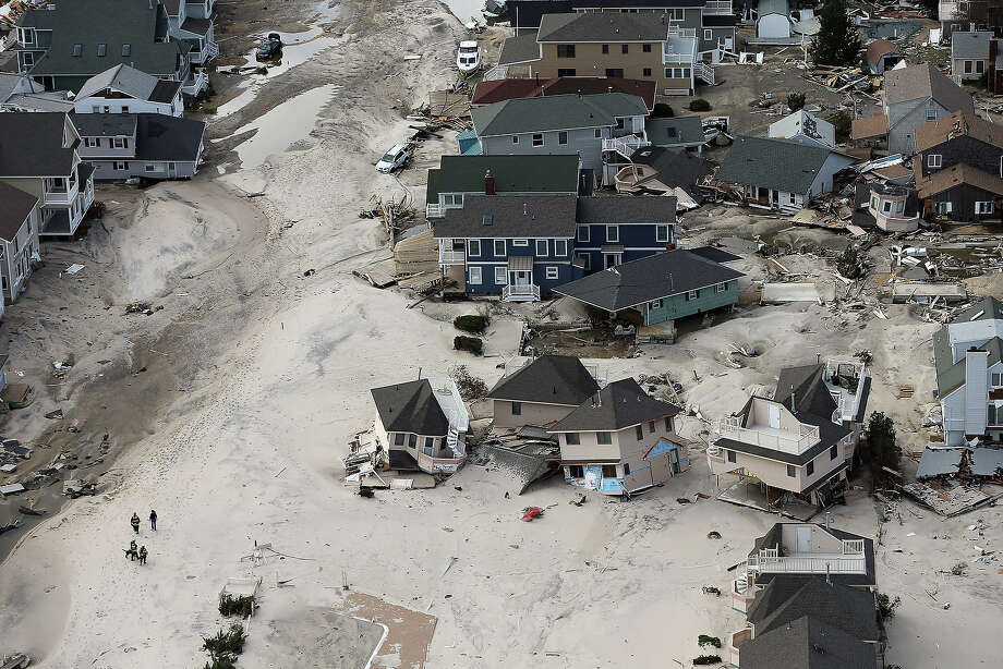 SEASIDE HEIGHTS, NJ - OCTOBER 31:  Rescue workers (LOWER L) walk past homes wrecked by Superstorm Sandy on October 31, 2012 in Seaside Heights, New Jersey. At least 50 people were reportedly killed in the U.S. by Sandy with New Jersey suffering massive damage and power outages. Photo: Mario Tama, Getty Images / 2012 Getty Images
