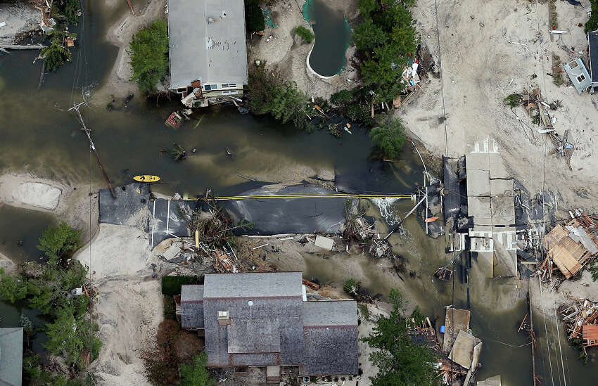 MANTOLOKING, NJ - OCTOBER 31: The remains of a road are mired in debris and water from Superstorm Sandy on October 31, 2012 in Mantoloking, New Jersey. At least 50 people were reportedly killed in the U.S. by Sandy with New Jersey suffering massive damage and power outages.