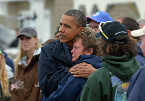 US President Barack Obama comforts Hurricane Sandy victim Dana Vanzant as he visits a neighborhood in Brigantine, New Jersey, on October 31, 2012. Americans sifted through the wreckage of superstorm Sandy on Wednesday as millions remained without power. The storm carved a trail of devastation across New York City and New Jersey, killing dozens of people in several states, swamping miles of coastline, and throwing the tied-up White House race into disarray just days before the vote. AFP PHOTO/Jewel Samad Photo: JEWEL SAMAD, AFP/Getty Images / 2012 AFP