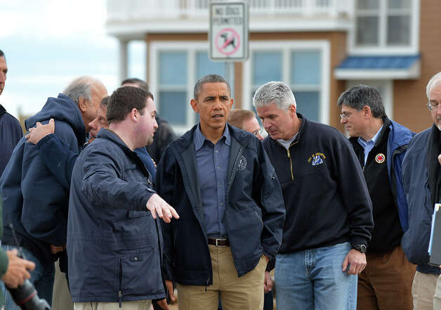 US President Barack Obama (C) listens to local officials on October 31, 2012 as he visits a neighborhood in Brigantine, New Jersey hit by Hurricane Sandy. Americans sifted through the wreckage of superstorm Sandy on Wednesday as millions remained without power. The storm carved a trail of devastation across New York City and New Jersey, killing dozens of people in several states, swamping miles of coastline, and throwing the tied-up White House race into disarray just days before the vote. AFP PHOTO/Jewel Samad Photo: JEWEL SAMAD, AFP/Getty Images / 2012 AFP