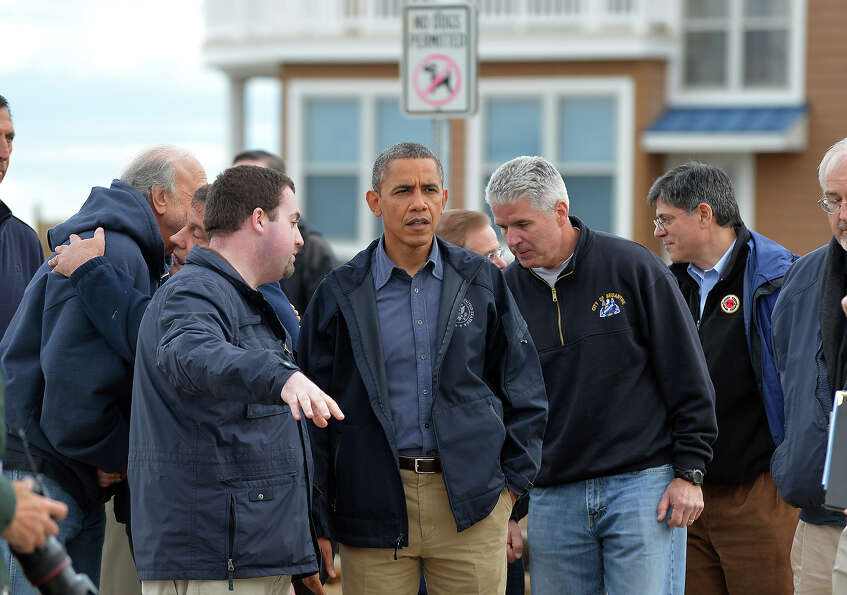 US President Barack Obama (C) listens to local officials on October 31, 2012 as he visits a neighbor