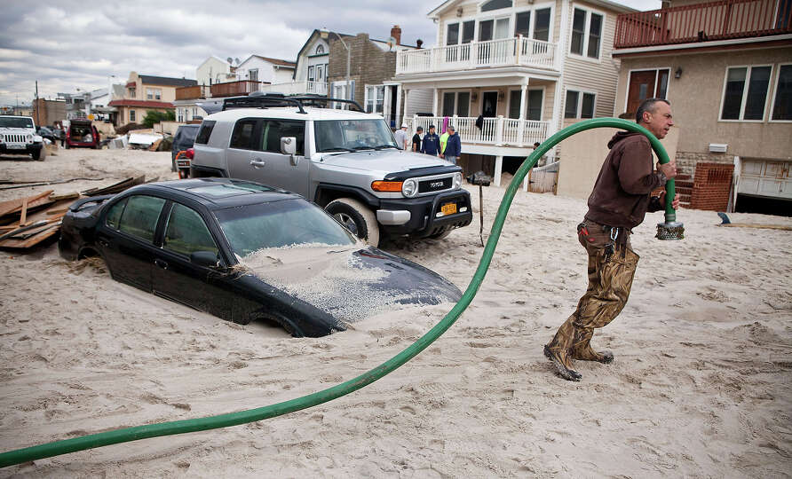 LONG BEACH, NY - OCTOBER 31:  Robert Justh drags a hose while attempting to drain a flooded basement