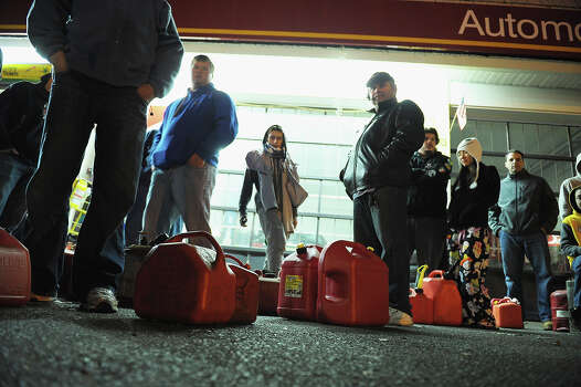 SAYREVILLE, NJ - OCTOBER 31:  People wait in line with gas canisters at a Getty gas station on October 31, 2012 in Sayreville, New Jersey. Many gas stations in Middlesex, Monmouth and Ocean counties, and elsewhere in New Jersey are closed and sold out of gasoline due to extensive power outages caused by Hurricane Sandy. Photo: Michael Loccisano, Getty Images / 2012 Getty Images