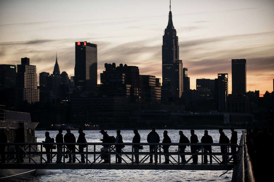People board the NY Waterways ferry with the Manhattan skyline in the background November 1, 2012 in Hoboken, New Jersey. Hurricane Sandy, which made landfall along the New Jersey shore, left parts of the state and the surrounding area without power including much of lower Manhattan south of 34th Street. AFP PHOTO/Brendan SMIALOWSKI Photo: BRENDAN SMIALOWSKI, AFP/Getty Images / 2012 AFP