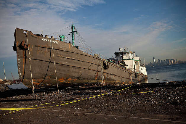 NEW YORK, NY - NOVEMBER 01:  The John B. Caddell tanker is docked along the Staten Island water front while the Manhattan skyline shines in the background on November 1, 2012 in New York City. Superstorm Sandy, which has left millions without power or water, continues to effect business and daily life throughout much of the eastern seaboard. Photo: Andrew Burton, Getty Images / 2012 Getty Images