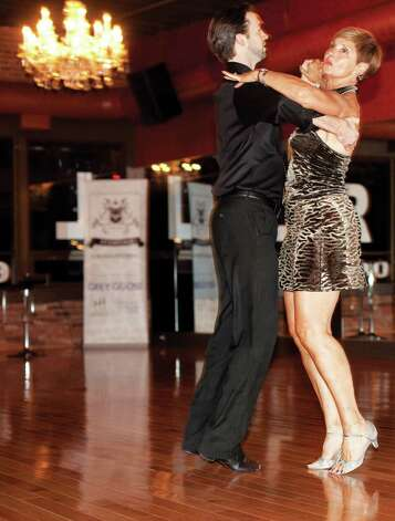 Linda Succi practices her ballroom technique with David Thomas Moore, general manager and instructor at Dance With Me in Stamford. Photo: Wendy Carlson / Healthy Life