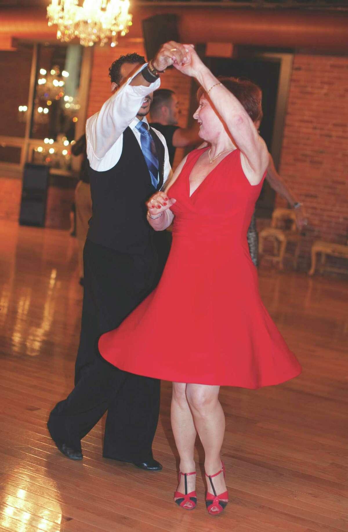 Instructor Edwardo Rojas dances with Agi Hale during a post-lesson dance party.