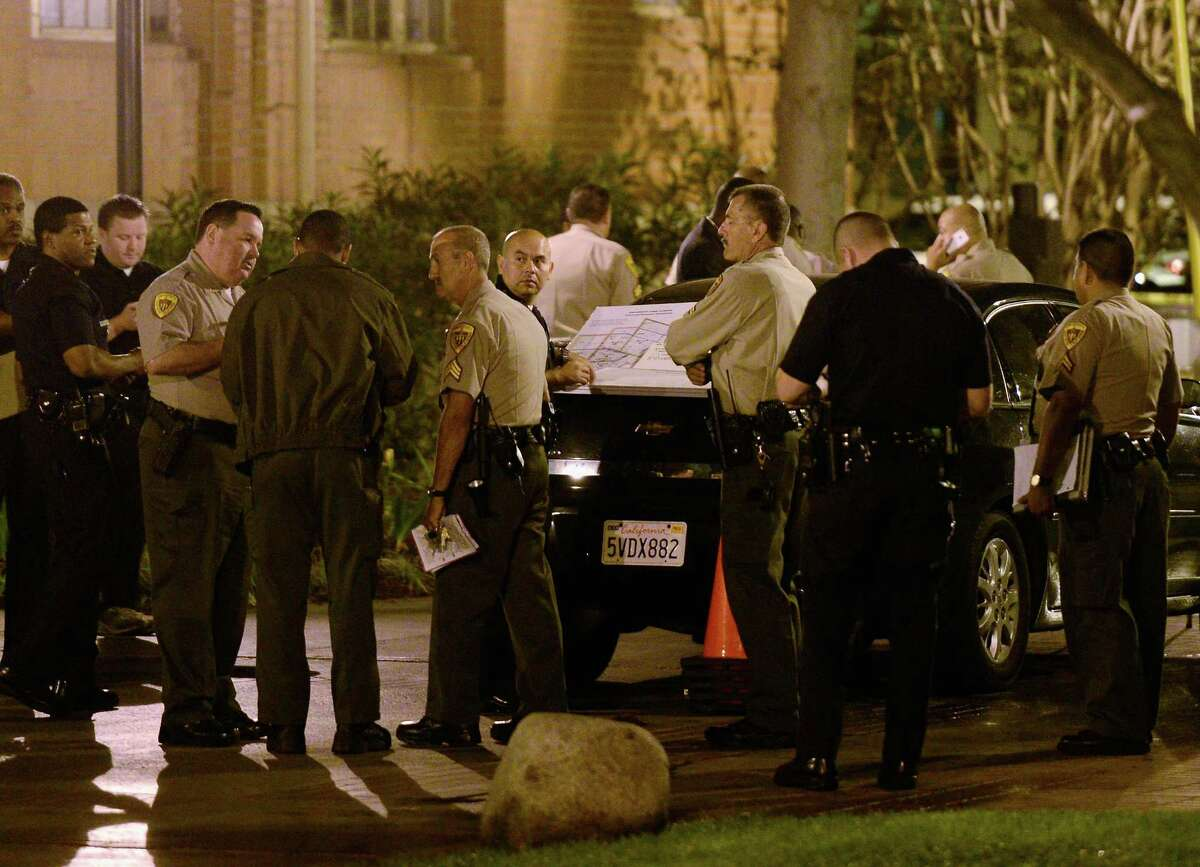 Los Angeles Police Department officers and USC Department of Public Safety officer gather at the command post after four people were shot including one in critical condition during a Halloween party at the Tutor Campus Center.