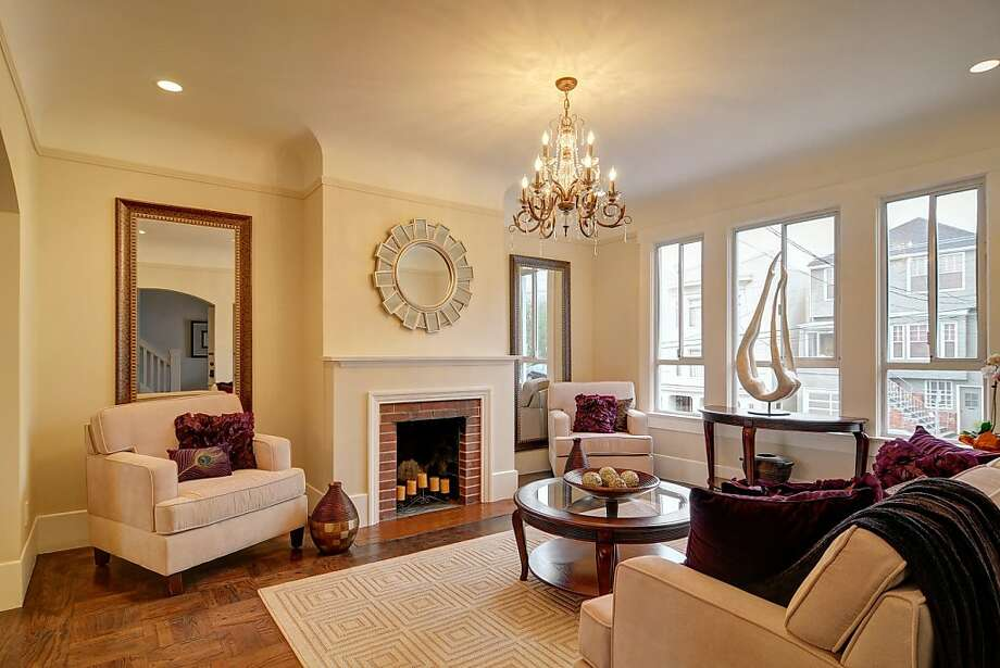 The home opens into a comfortable living room featuring a fireplace and large windows facing the street. Photo: Scott DuBose