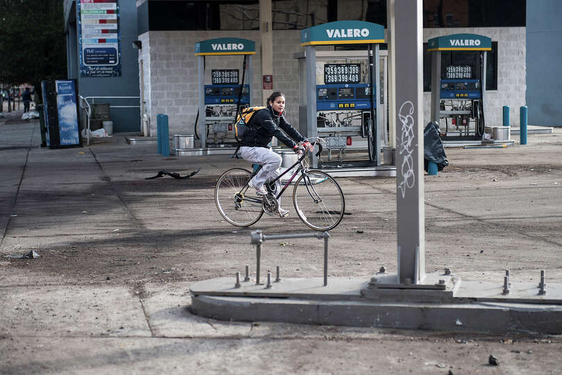 A woman rides her bike through a closed gas station that was recently below flood waters on November
