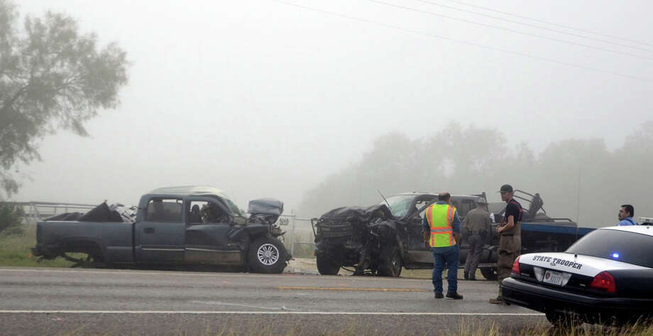 State troopers and emergency crews canvas a crash scene where two people died and four others injured this morning when two pickups collided head-on in Atascosa County. Another vehicle also was involved in the accident. The crash happened on Texas 16 near Jourdanton on Thursday, Nov. 1, 2012. Photo: Jack Garcia, For The Express-News / Jack Garcia/ For the San Antonio