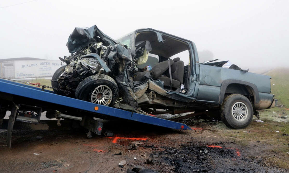 A demolished truck is removed from a crash scene where two people died and four others injured this morning when two pickups collided head-on in Atascosa County. Another vehicle also was involved in the accident. The crash happened on Texas 16 near Jourdanton on Thursday, Nov. 1, 2012.