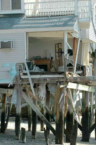 Just a year ago, Tropical Storm Irene ripped out a livingroom wall of a home at the end of Fairfield Beach Road. Photo: Cathy Zuraw