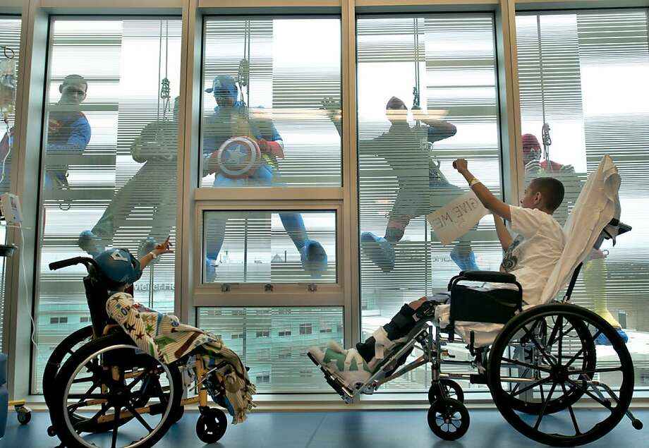 """Halloween treat:Four-year-old Connor Videtich and 13-year-old Randall """"Rico"""" Simmons wave to Captain America, the Flash, Spider-Man and other superheroes fighting crime on the ninth floor of DeVos Children's Hospital in Grand Rapids, Mich. Window washers and a hospital specialist came up with the idea to give the young patients a surprise. Photo: Chris Clark, Associated Press"""