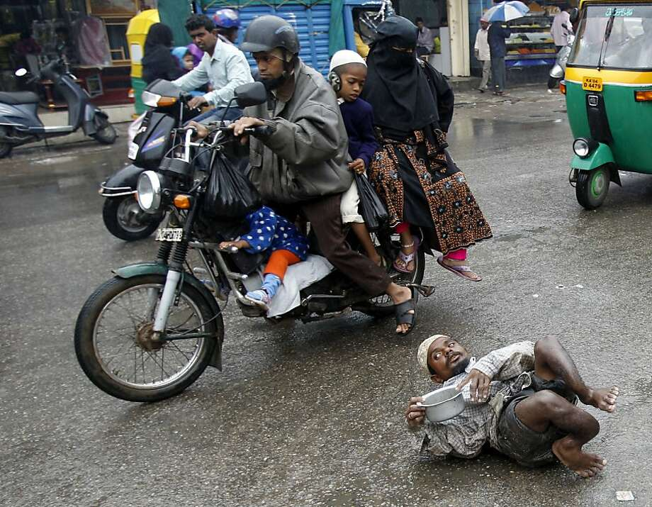 A motorcycle carrying an entire familypasses a disabled man named Abdul begging for alms in the rain in Bangalore, India. Photo: Aijaz Rahi, Associated Press